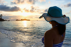 Girl on the beach at sunrise. Girl with blue and white striped swimsuit standing watch nature sky and sea during the sunrise on beach of Honeymoon Bay at Koh Royalty Free Stock Images
