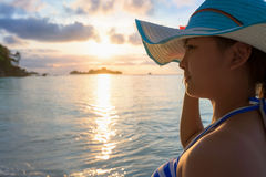 Girl on the beach at sunrise. Girl with blue and white striped swimsuit standing watch nature sky and sea during the sunrise on beach of Honeymoon Bay at Koh Stock Images