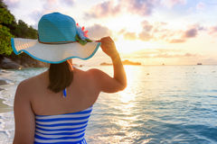 Girl on the beach at sunrise. Girl with blue and white striped swimsuit standing watch nature sky and sea during the sunrise on beach of Honeymoon Bay at Koh Stock Photo