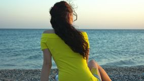 The girl on the beach at sunset. A lonely girl sits by the sea on a pebble beach and admires the sunset stock video