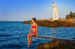 Girl at beach sunset on trampoline royalty free stock image