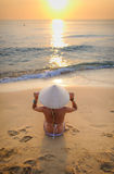 girl on beach at sunset wearing a rice-hat 2 Stock Photo