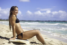 Girl on the beach with surfboard. Blond girl in bikini sitting on her surfboard on the beach in hawaii Stock Images