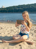 Girl on the beach with the tablet Stock Images