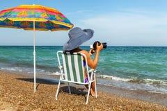 A girl on a beach takes pictures a sea stock photos