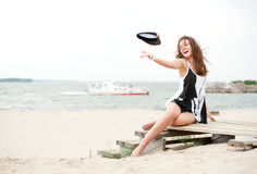 Girl on beach throwing his cap and laughs Royalty Free Stock Images
