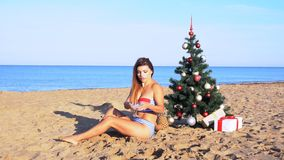 Girl on the beach under the Christmas tree for Christmas in the tropics. 1 stock footage