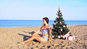Girl on the beach under the Christmas tree for Christmas in the tropics. 1 stock video