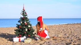 Girl on the beach under the Christmas tree for Christmas in the tropics stock footage