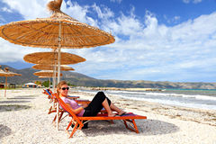 Girl on the beach under a parasol. A pretty girl with sunglasses  looking into the camera lying on a beach couch under a straw parasol enjoys a quiet summer day Stock Photo
