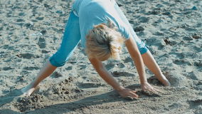 Girl on the beach by the water on sand draws stock footage