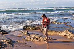 Girl Beach Waves Exploring. Teen girl unidentified exploring nature marine life on beach towel looking at ocean waves and reefs royalty free stock image