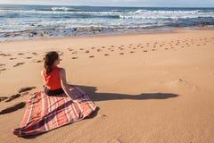 Girl Beach Waves Towel. Teen girl unidentified relaxing sitting on beach towel looking at ocean waves and reefs royalty free stock image