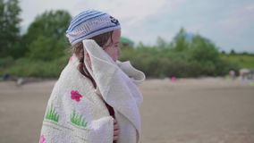 A girl on the beach wipes the body with a towel after bathing. Summer holidays, rest by the sea. Summer holidays, rest by the sea. A girl on the beach wipes the stock footage