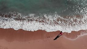 Girl on beach. Woman in red dress walking on sandy beach. Young attractive girl walking down the beach. Aerial view of sandy beach stock footage