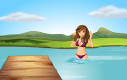 A girl at the beach with a wooden diving board Stock Image