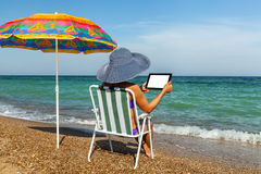 A girl on a beach works on a plane-table stock photography