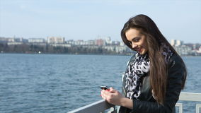 Girl on the beach writing sms stock video