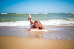 Girl on the beach. Young girl is lying on the beach in the waves Royalty Free Stock Photo