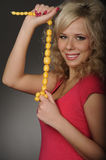 Girl with beads. Beautiful magnificent woman in  red shirt with yellow beads on dark background Stock Photos