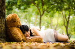 The girl with a bear. Cute asian girl resting under a tree with a teddy bear Royalty Free Stock Images