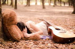 The girl with a bear. Cute asian girl resting under a tree with a teddy bear Stock Photo