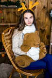 Girl with bear in her hand sitting in the room with wooden walls Royalty Free Stock Image