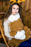 Girl with bear in her hand sitting in the room with wooden walls Stock Photos