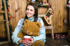 Girl with bear in her hand sitting in the room with wooden walls Stock Photo
