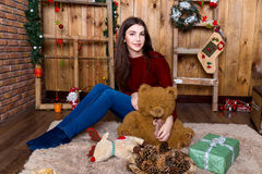 Girl with bear in her hand sitting in the room with wooden walls Royalty Free Stock Images