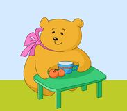Girl-bear with peaches. The girl-bear sits at a table, eats peaches and drinks juice from a mug Stock Image