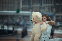 Girl with a bear during snow. Royalty Free Stock Photo