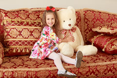 Girl with bear on sofa Stock Photography