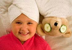 Girl and bear in towels. Little girl with her hair wrapped in a white towel next to her bear wrapped in a towel with cucumbers on its eyes royalty free stock photography