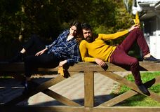 Girl and bearded guy lie on handrail back to back. Girl and bearded guy lie on wooden handrail back to back. Couple in love spends time in park. Woman and men stock image