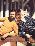 Girl and bearded guy lie on handrail back to back. Girl and bearded guy lie on wooden handrail back to back. Relaxation and relationship concept. Couple in love stock photo