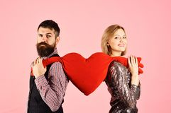 Girl and bearded man with smiling faces divide toy heart. Girl and bearded men with smiling faces divide soft toy heart with hands. Boyfriend and girlfriend have royalty free stock photos