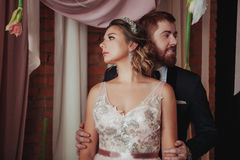 Girl and bearded red man standing near the ceremonial arches with fabrics, fresh flowers on a background of brick wall. Girl and bearded red men standing near Royalty Free Stock Image
