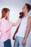 Girl beating boy. Rude girl beating her friend with boxing gloves Stock Photo