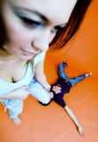 Girl Beating Guy. Playful girl standing with foot on guy who is sprawled out on floor royalty free stock photos