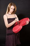 Girl beating red heart with knife. Over black background royalty free stock images