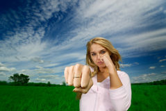 Girl beats a fist. The young beautiful woman beats a fist towards to  camera against  nature Royalty Free Stock Image