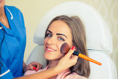 Girl with a beautician at spa salon. Beautician performs cosmeti Stock Photography
