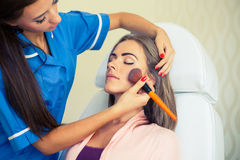 Girl with a beautician at spa salon. Beautician performs cosmeti Stock Photos