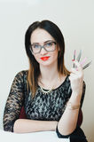 The girl is a beautician tools. The girl beautician sitting in bright office, glasses, tools in the hands of Stock Photo