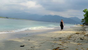 A girl in beautiful black dress walking and running by the sea. Girl in elegant black dress walking and running by beautiful sea in Gili Air island, Indonesia stock video