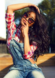 Girl with beautiful black hair in sunglasses sits. Girl with beautiful black hair in sunglasses Stock Photos