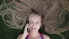 Girl with beautiful blonde hair lying on grass stock video footage
