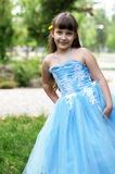 Girl in a beautiful blue dress. A little girl with a yellow dandelion behind his ear Stock Photo