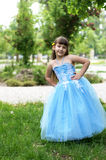 Girl in a beautiful blue dress. A little girl with a yellow dandelion behind his ear Royalty Free Stock Photos